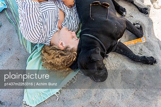 Junge Frau und Hund schlafen am Strand - p1437m2283316 von Achim Bunz