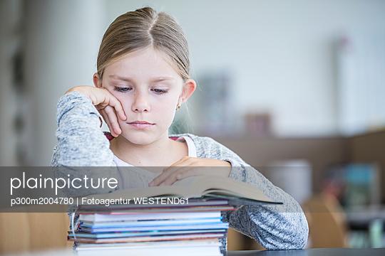 Schoolgirl reading book on table in school - p300m2004780 von Fotoagentur WESTEND61