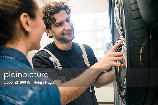 Smiling car mechanic and client looking at tire in workshop - p300m2166815 by Robijn Page