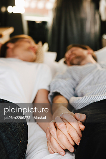 Gay couple holding hands while lying down in motor home during vacation - p426m2296273 by Maskot