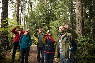 Active senior friends hiking, using camera phones in woods - p1192m2000432 by Hero Images