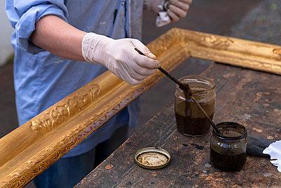 Frame-maker in workshop patinating Baroque wooden frame - p300m1023367f by Tom Chance