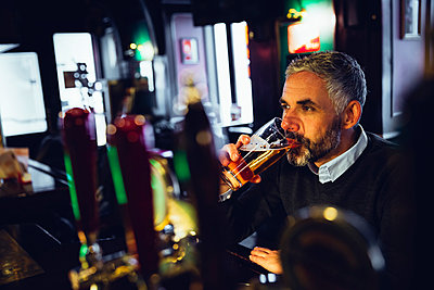 Man sitting at counter of a pub drinking beer - p300m1023429f by Martin Benik
