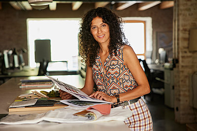Female fashion designer holding fabric swatch in office - p300m2294123 by Rainer Berg