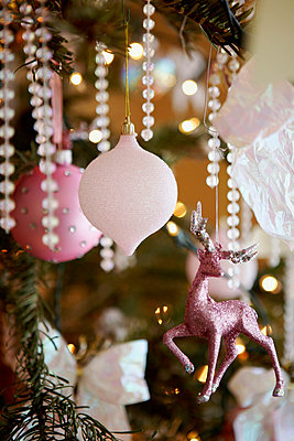 Pink baubles and reindeer decoration on Christmas tree - p349m789727 by Brent Darby