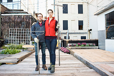 Couple holding rakes in urban rooftop garden - p555m1304764 by Jasper Cole