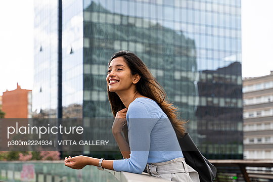 Smiling businesswoman looking away while leaning on railing against modern building - p300m2224934 by VITTA GALLERY