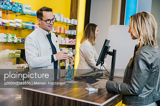Smiling female customer giving prescription to salesman in chemist store - p300m2243836 by Mareen Fischinger