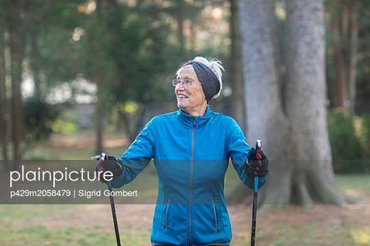 Senior woman nordic walking in park - p429m2058479 by Sigrid Gombert