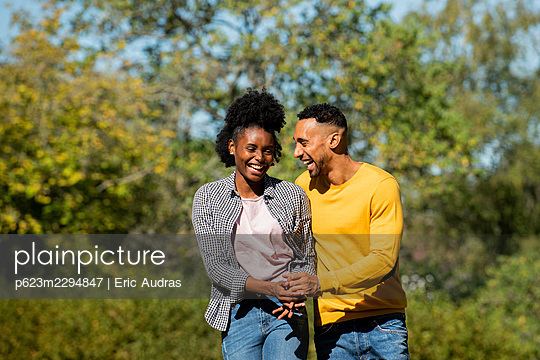 Smiling young couple having fun while walking in public park - p623m2294847 by Eric Audras
