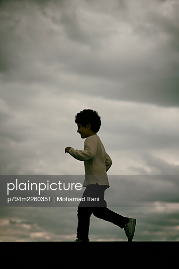 Side view of little boy running away outdoors  - p794m2260351 von Mohamad Itani