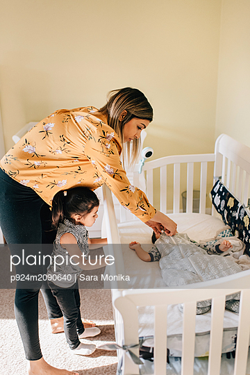 Girl and mother putting baby brother in crib - p924m2090640 by Sara Monika