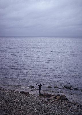 Mann mit ausgestreckten Armen am Meer - p1124m1193529 von Willing-Holtz