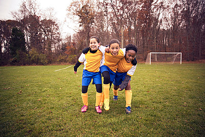 Full length of soccer players enjoying on playing field against trees - p1166m1038258f by Cavan Images