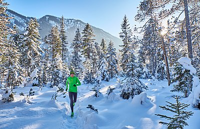 Germany, Bavaria, Isar valley, Vorderriss, woman jogging in winter forest - p300m1356273 by Michael Reusse (alt)
