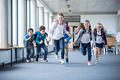 Excited pupils rushing down school corridor - p300m2005292 von Fotoagentur WESTEND61