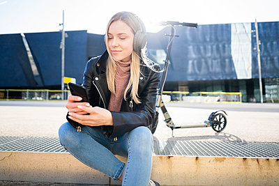 Portrait of young woman listening music with smartphone and headphones, Barcelona, Spain - p300m2119879 by Giorgio Fochesato
