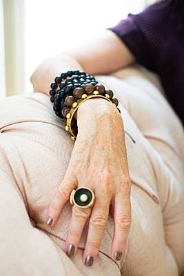 Stylish mature woman wearing bead bracelets and ring, close up of hand - p924m2074546 by Sioux Nesi