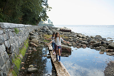 Girl friends walking, balancing on fallen log over water - p1192m1511818 by Hero Images