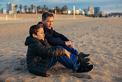 Father and son sitting on the beach - p300m1562888 by Bonninstudio