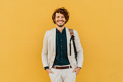 Portrait of laughing businessman with backpack standing in front of yellow wall - p300m2113851 by VITTA GALLERY