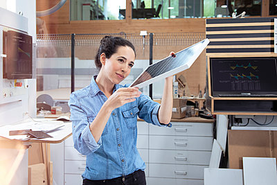 Female entrepreneur analyzing solar panel model in factory - p300m2265980 by Florian Küttler