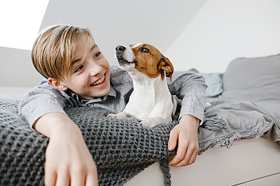 Smiling boy with arm around dog lying on bed at home - p300m2276027 by Katharina Mikhrin