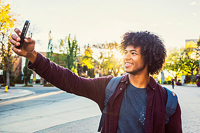 A young male African American university student poses for a self-portrait with his smart phone; Edmonton, Alberta, Canada - p442m2004163 by LJM Photo