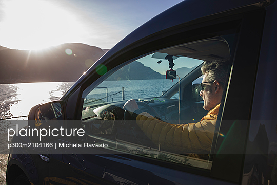 Italy, Como, man sitting in car while crossing the lake on the ferry - p300m2104166 by Michela Ravasio