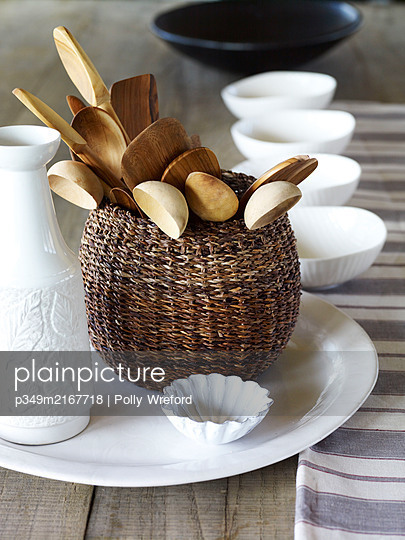 Basket of wooden spoons with white ceramic homeware - p349m2167718 by Polly Wreford