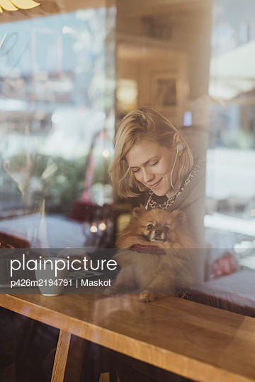 Smiling blond woman sitting with Pomeranian at cafe seen through window - p426m2194791 by Maskot