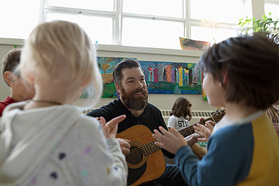 Male teacher with guitar teaching preschool students in classroom - p1192m1560127 by Hero Images