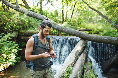 Young man holding cell phone at a waterfall in forest - p300m1505521 by Vasily Pindyurin
