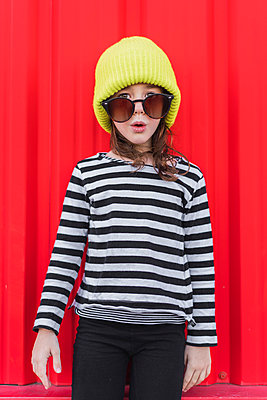 Portrait of astonished little girl wearing striped shirt, yellow cap and oversized sunglasses - p300m2103015 by Eloisa Ramos