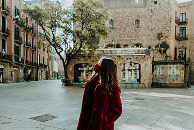 Woman wearing face mask looking away while standing against building at Gothic Quarter during isolation, Barcelona, Spain - p300m2188657 by Gala Martínez López