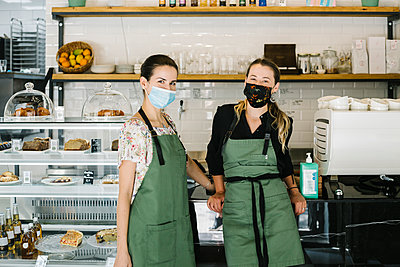 Partners wearing face mask and apron standing by counter at coffee shop - p300m2227343 by Xavier Lorenzo