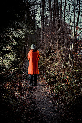 Woman takes a walk in the forest at dusk - p750m1496896 by Silveri