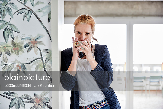 Woman drinking coffee while leaning on wall against window at home - p300m2266034 by Jo Kirchherr