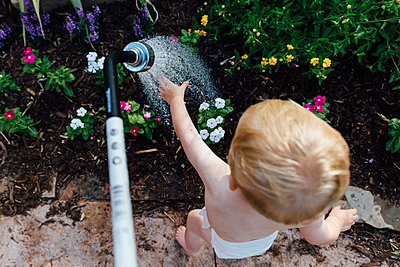 Rear view of shirtless baby boy playing with water while standing by plants at yard - p1166m2009638 by Cavan Images