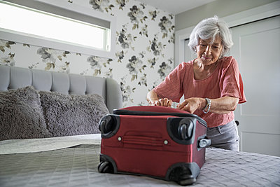 Senior woman packing suitcase on bed - p1192m2109889 by Hero Images