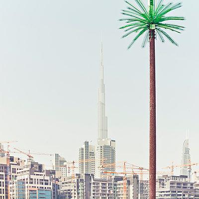Palm shaped lantern against Burj Khalifa with skyline of Dubai - p1542m2142350 by Roger Grasas
