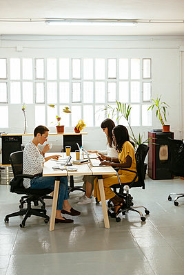 Colleagues working at desk in office - p300m2079530 by Bonninstudio