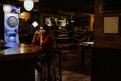 Mid adult woman drinking beer while sitting at table in restaurant - p300m2206838 by DREAMSTOCK1982