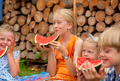 Germany, Bavaria, Group of children eating watermelon - p300m752372f by hsimages