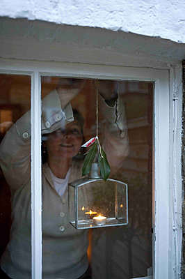 Woman hangs candle in lantern at window of Richmond home - p349m790869 by Polly Eltes