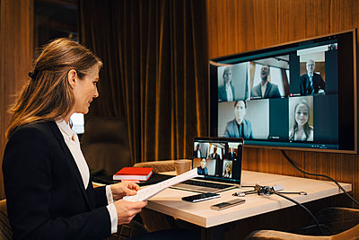 Businesswoman discussing with male and female colleagues on video call through laptop in office - p426m2270835 by Maskot