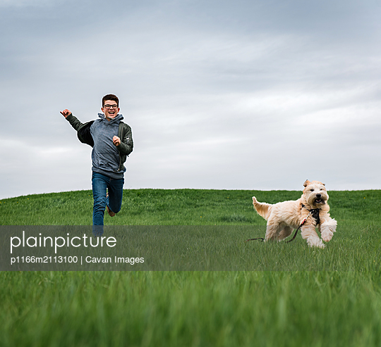Teenage boy running across a grassy field with his dog on cloudy day. - p1166m2113100 by Cavan Images