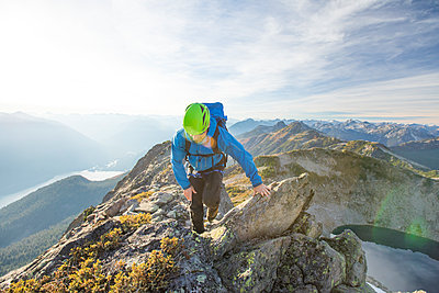 Backpacker scrambles across rocky ridge, British Columbia, Canada. - p1166m2095218 by Cavan Images