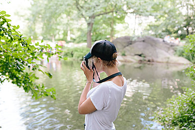 Young woman with a vintage camera taking pictures in park - p300m1356169 by Boy photography