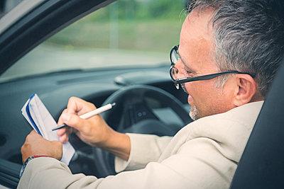 Businessman sitting in his car making notes - p300m1505356 by JLPfeifer